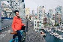 Portrait d'une jeune femme prête à faire du vélo sur une piste cyclable, Vancouver, Colombie-Britannique, Canada — Photo de stock