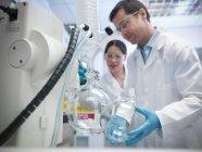 Scientifiques masculins et féminins travaillant avec le vide encore en laboratoire, scientifique masculin tenant récipient en verre — Photo de stock