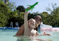 Mother and son playing in swimming pool — Stock Photo