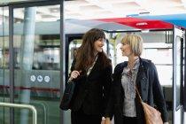 Mujeres de negocios caminando cerca de la estación de autobuses, enfoque selectivo - foto de stock