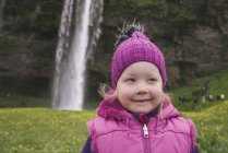 Portrait of young girl in field, waterfall in background, Seljalandsfoss, Iceland — Stock Photo