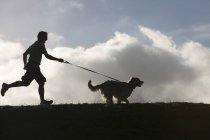 Man running with dog on lead — Stock Photo