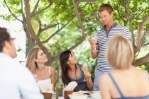 Friends drinking wine at table outdoors — Stock Photo
