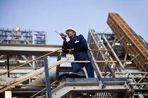Travailleur utilisant talkie walkie sur place — Photo de stock