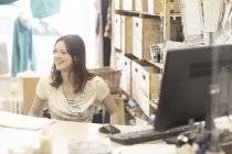 Young female shop assistant using wheelchair behind shop checkout — Stock Photo