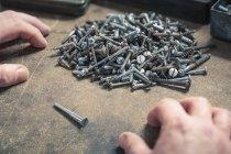 Paire de mains, une vis se démarquant des tas de vis de tailles différentes — Photo de stock