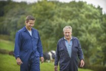Agricultor e filho caminhando juntos no campo — Fotografia de Stock