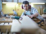 Homme travaillant le bois en atelier — Photo de stock