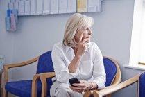 Зрелая пациентка с мобильным телефоном в приемной больницы — стоковое фото