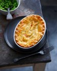 Dish of baked pie and peas — Stock Photo