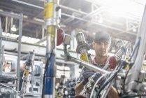 Рабочий в защитных очках, осматривающий автомобильные детали на автомобильном заводе — стоковое фото