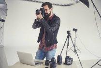 Fotógrafo masculino probando el enfoque digital Delr para la foto de estudio - foto de stock