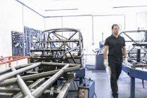 Ingenieur mit Rennwagen Rollcontainer im Rennsport Autofabrik — Stockfoto