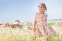 Girl standing in tall grass outdoors — Stock Photo