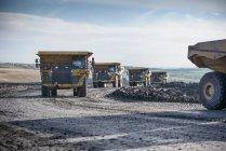 Dumpers dirigindo na pista na mina de carvão de superfície — Fotografia de Stock