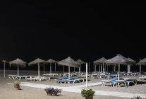 Vacío de tumbonas en la playa en la noche - foto de stock