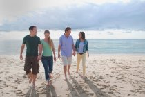 Couples holding hands on beach — Stock Photo