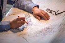 Architect drawing plans at drawing board, close up — Stock Photo