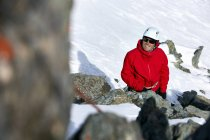 Mountaineer on snow covered mountain looking up smiling, Saas Fee, Switzerland — Stock Photo
