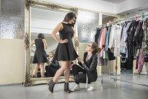 Модельер работает вместе с клиентом в студии моды — стоковое фото