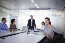 Portrait of businesswoman with colleagues at boardroom table — Stock Photo