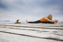Середині дорослу жінку заняттях йогою на дерев'яні морський Пірс — стокове фото