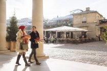 Casal jovem carregando presentes de Natal passeando por Covent Garden, Londres, Reino Unido — Fotografia de Stock