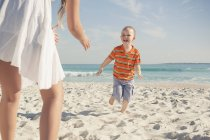 Mother playing with young son on beach — Stock Photo