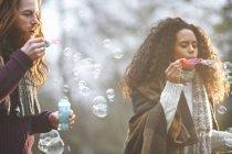 Couples soufflant des bulles de savon dans la campagne — Photo de stock