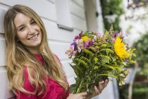 Portrait of young woman with bunch of flowers — Stock Photo