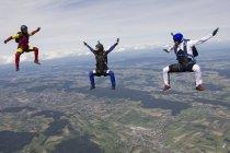 Equipe de três pára-quedistas em posição de voo sentado sobre Buttwil, Luzern, Suíça — Fotografia de Stock