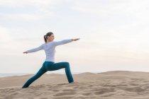 Woman practicing yoga warrior pose on dune, Maspalomas, Gran Canaria, Canary Islands, Spain — Stock Photo