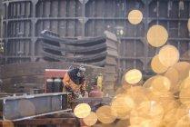 Lavoratore che macina la costruzione del metallo nella fabbrica di fabbricazione marina — Foto stock