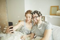 Mid adult couple covered in pillow fight feathers taking smartphone selfie in bed — Stock Photo