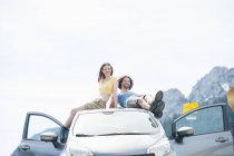 Mid adult couple relaxing on car roof, Wallberg, Tegernsee, Bavaria, Germany — Stock Photo