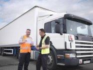 Motorista de caminhão estagiário recebendo certificado de passagem do instrutor — Fotografia de Stock