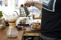 Hand of cafe waiter pouring boiling water into filter coffee pot — Stock Photo