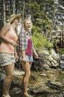 Mujer joven y adolescente remando en el río bosque, Red Lodge, Montana, EE.UU. - foto de stock