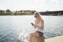 Junge Frau sitzt am Flussufer und textet auf Smartphone, Donauinsel, Wien, Österreich — Stockfoto