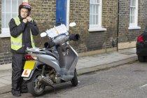 Male motor scooter rider in street fastening crash helmet — Stock Photo