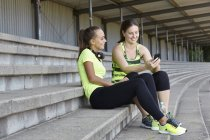 Two young female runners chatting in stadium seating — Stock Photo