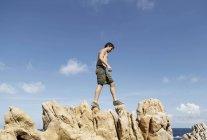 Vue de côté du faible angle de jeune homme escalade sur rochers, Costa Paradiso, Sardaigne, Italie — Photo de stock