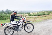 Mid adult female motorcyclist riding on dirt track — Stock Photo