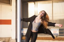 Smiling young woman swinging on pole in parking lot — Stock Photo