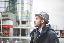 Vista lateral do homem de chapéu andando na cidade — Fotografia de Stock