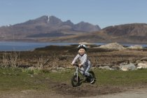 Boy riding bike, Lake Eishort, Isle of Skye, Hebrides, Scotland — Stock Photo