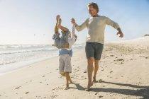 Отец и сын на пляже, взявшись за руки, размахивая мальчик — стоковое фото