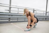 Jeune femme qui tente de chaussures, préparation pour la séance d'entraînement — Photo de stock