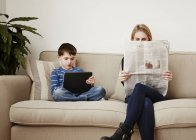 Young boy using digital tablet, mother reading newspaper — Stock Photo