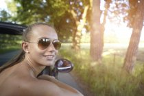 Young woman driving convertible looking over her shoulder — Stock Photo